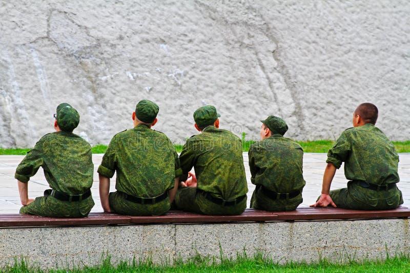 Giovani uomini dell'esercito che si siedono su un banco fotografie stock libere da diritti
