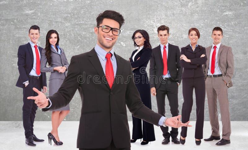 Uomo di affari che vi accoglie favorevolmente al suo riuscito gruppo immagini stock