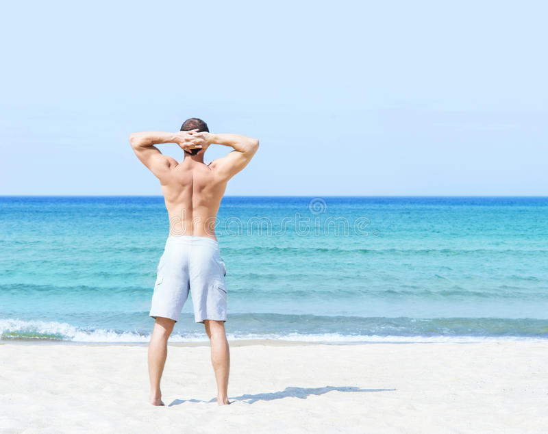 Giovani, uomo adatto che sta su una spiaggia di estate fotografia stock