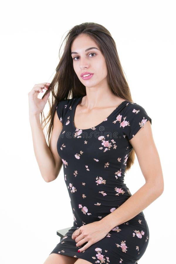 giovani vestiti neri casuali d'uso femminili della ragazza del vestito che posano sopra il fondo bianco fotografia stock libera da diritti