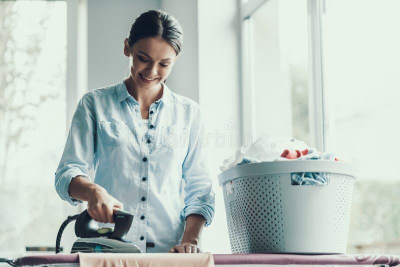 Giovani vestiti rivestenti di ferro sorridenti della donna dopo la lavanderia fotografia stock