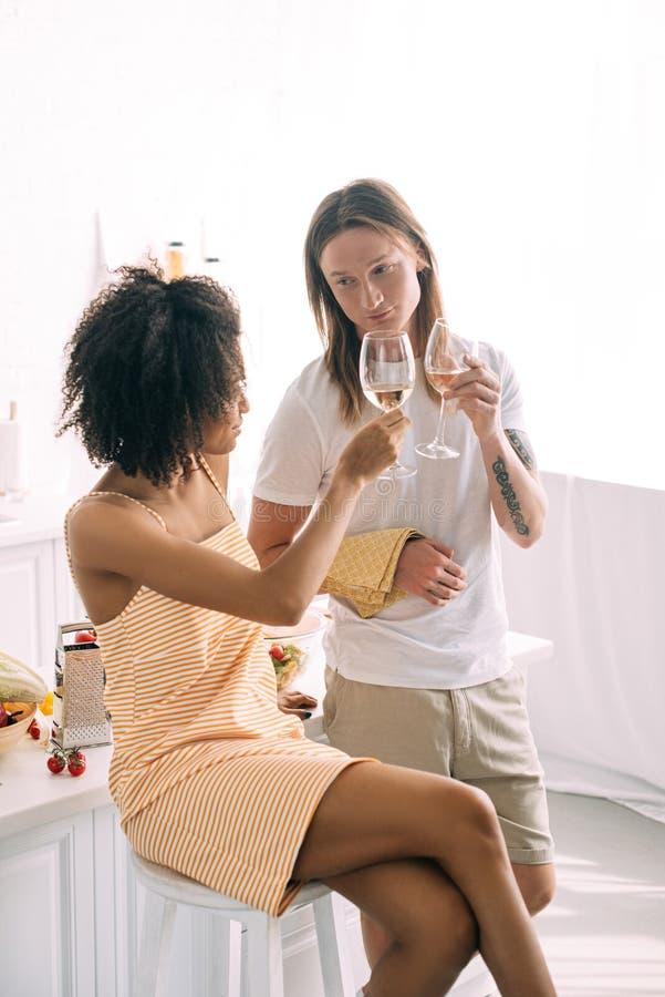 giovani vetri di vino bianco multietnici di tintinnio delle coppie fotografie stock