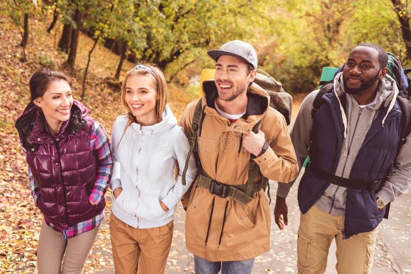 Giovani viaggiatori con zaino e sacco a pelo felici in foresta immagine stock