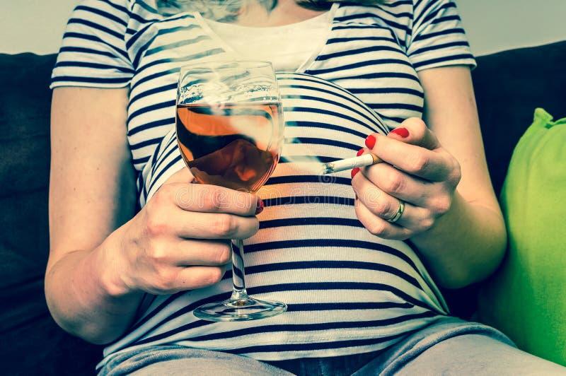 Giovani vino e sigaretta della tenuta della donna incinta immagine stock