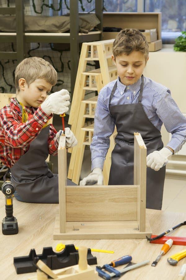 Giovani viti di chiusura dei ragazzi di scuola in panchetto di legno fotografia stock