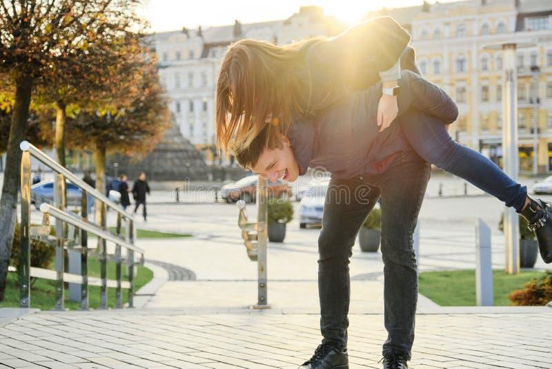Gioventù divertendosi nella città di primavera, il bello giovane divertente e la donna, ora dorata fotografia stock libera da diritti