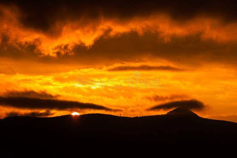 Gipfel und trasmitter auf Jested Berg versteckt in den Wolken Drastischer roter Himmel zur Sonnenuntergangzeit Liberec, Tschechis stockfotografie