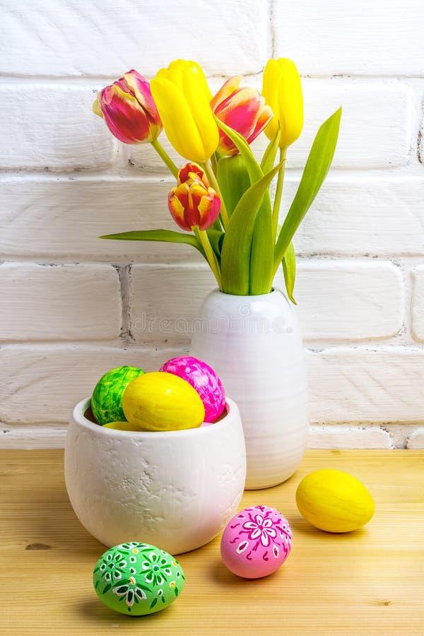 Gips-centrum med rosa, gröna, gula ägg och tulpaner fotografering för bildbyråer