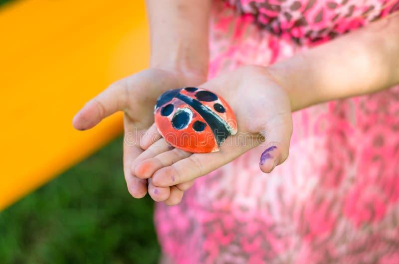 Gips ladybirs in den Kinderhänden stockbilder