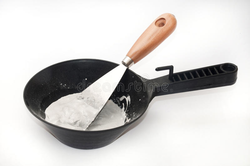 Gips und Wasser in einer schwarzen Schüssel mit einer Spachtel für das Mischen stockbild
