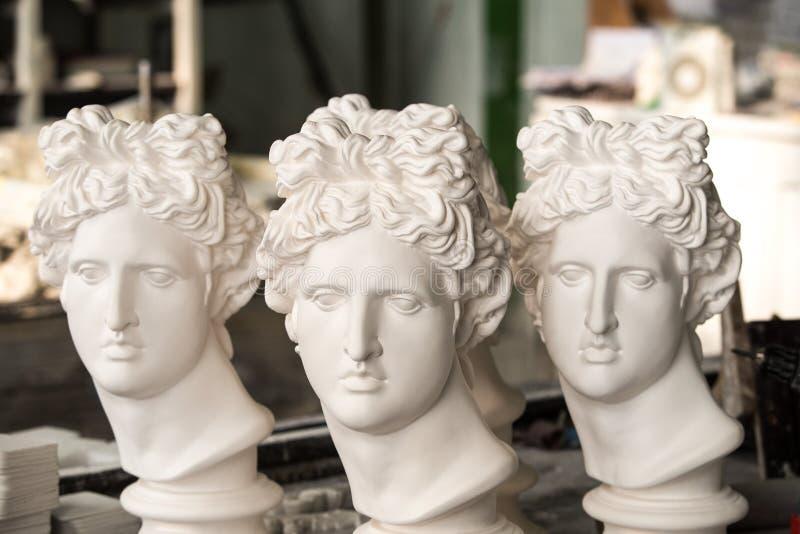 Gipsbeeldhouwwerken De hoofden van het gips Apollo in de workshop stock fotografie