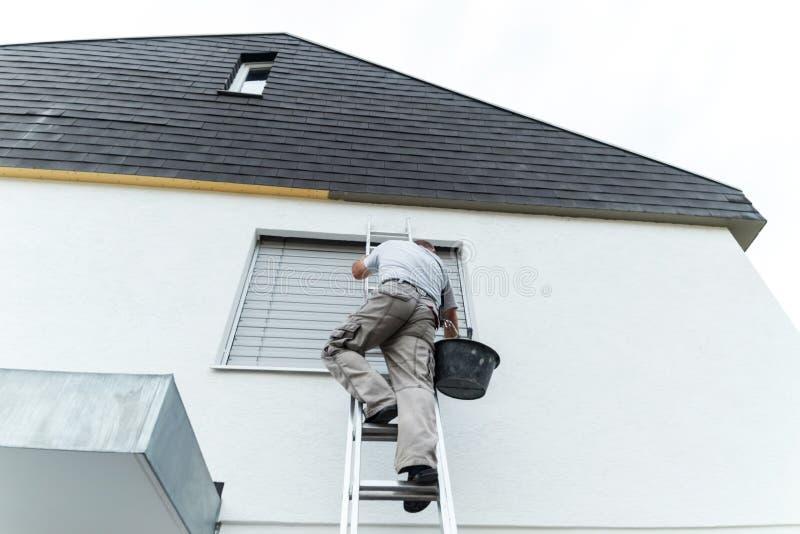 Gipser, der oben die Leiter klettert, um den Dachunterseitenesprit zu umfassen stockfoto