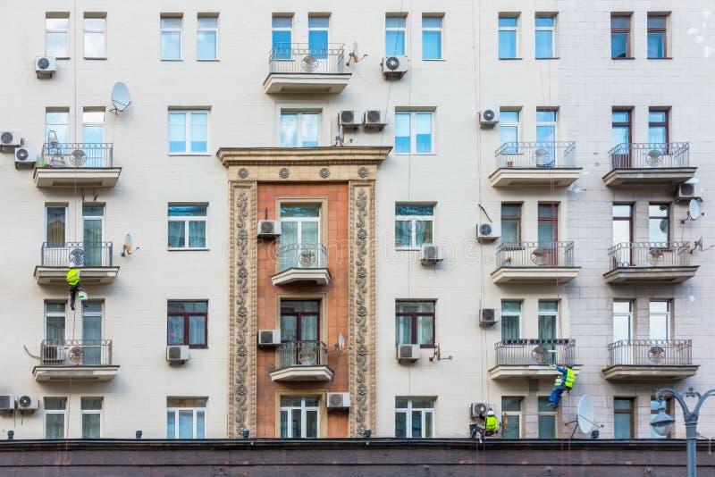 Gipsermaler drei, der die Fassade des Hauses repariert lizenzfreies stockfoto