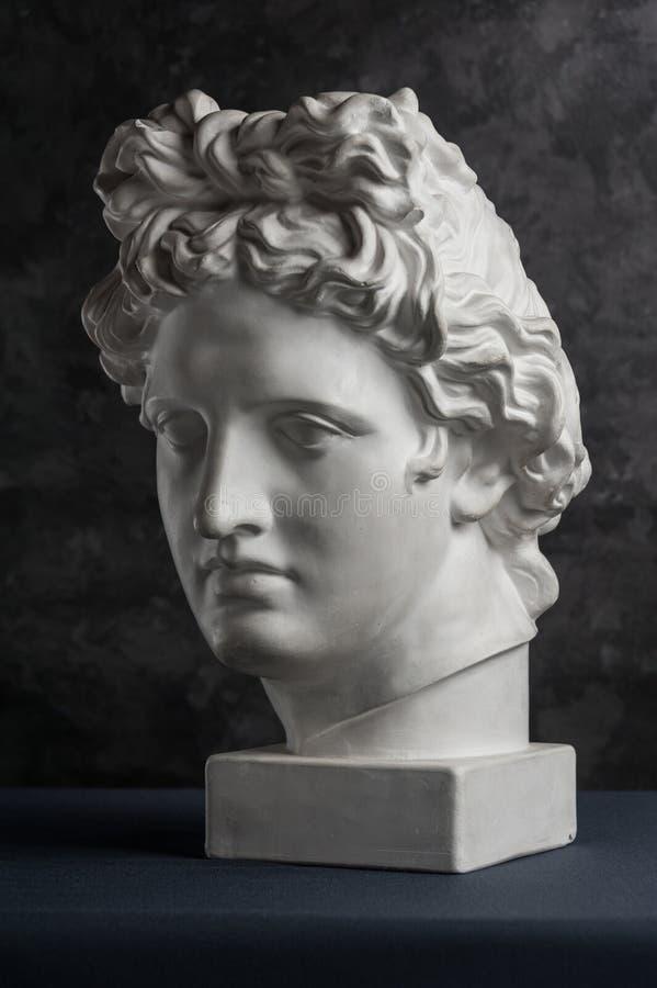 Gipskopie alten Statue Apollo-Kopfes auf dunklem strukturiertem Hintergrund Gipsskulptur-Manngesicht stockfotos