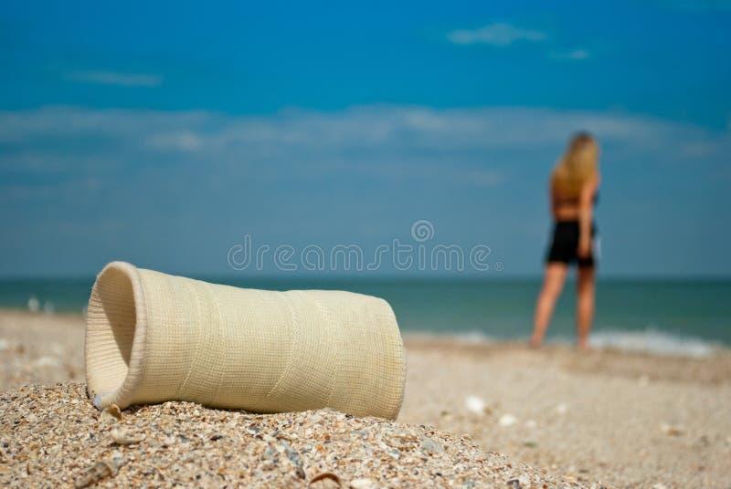 Gipsschuß, Mädchensandabschluß oben gegen das Meer und Himmel, bewölkt defektes Armglied, Wiederaufnahme, Mädchenblätter lizenzfreie stockbilder