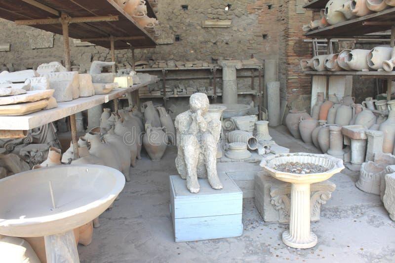 Gipsverbanden van slachtoffer van uitbarsting de Vesuvius en oud aardewerk in Pompei - oude Roman stad in Italië royalty-vrije stock foto's