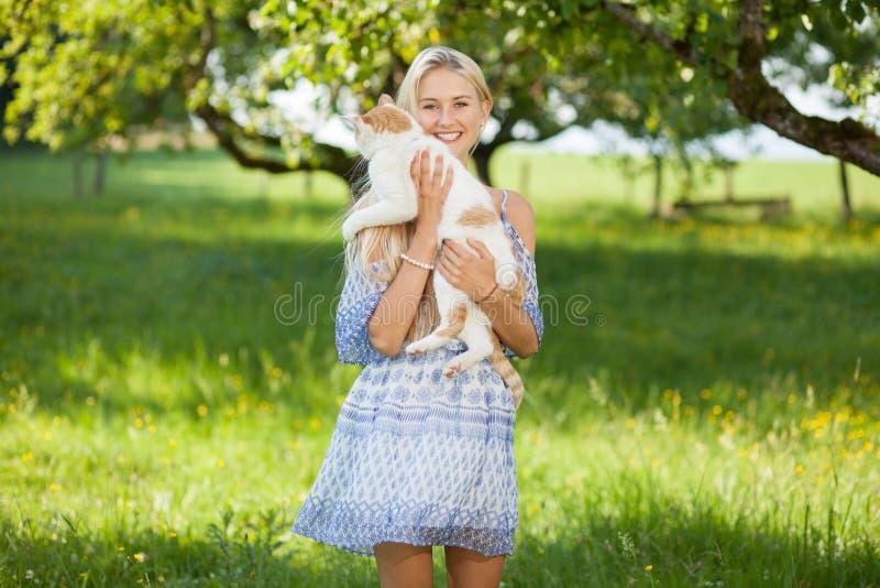Gir feliz en un prado de la flor del verano que sostiene un gato imagenes de archivo