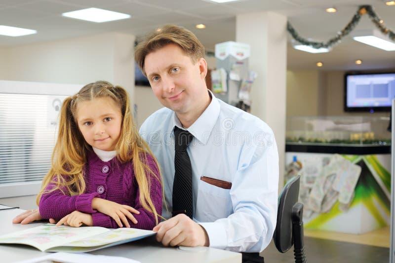 Gir feliz y su padre con el folleto del plan de piso en oficina. imagen de archivo libre de regalías