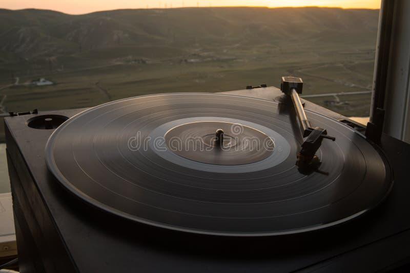 Giradischi del vinile della piattaforma girevole sui precedenti di un tramonto sopra le montagne Tecnologia sana affinchè il DJ m fotografie stock libere da diritti