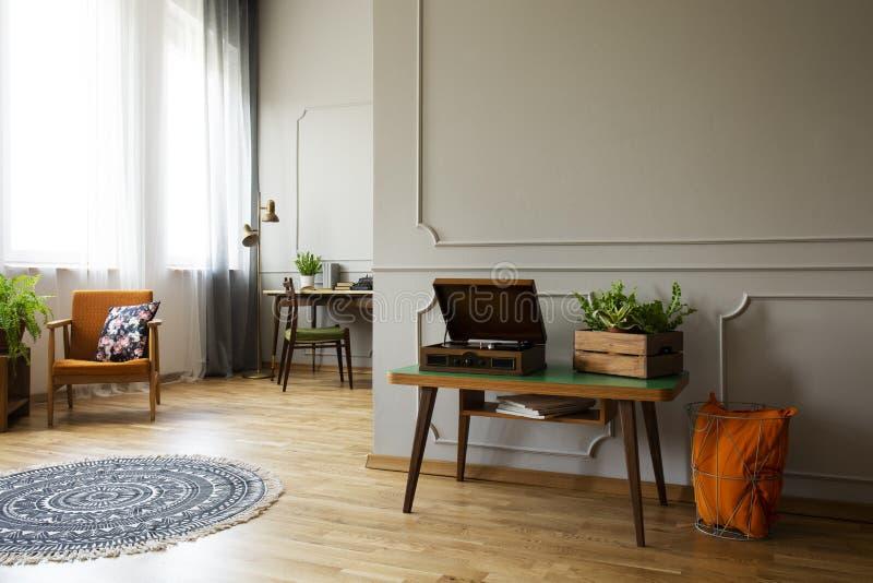 Giradischi e pianta sulla tavola nell'interno d'annata del salone con la coperta e la poltrona Foto reale fotografie stock libere da diritti