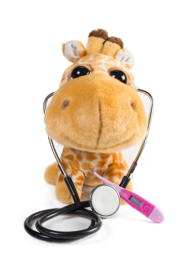 Girafe de jouet de peluche avec le stéthoscope et le thermomètre image stock