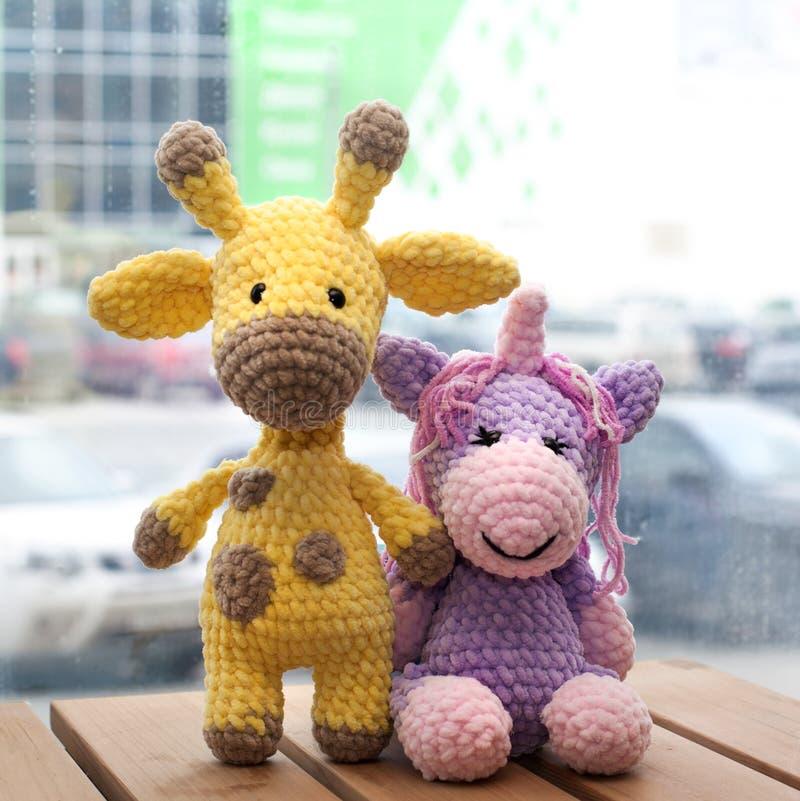 Girafe jaune et licorne d'amigurumi à crochet Jouet fait main tricot? photo stock