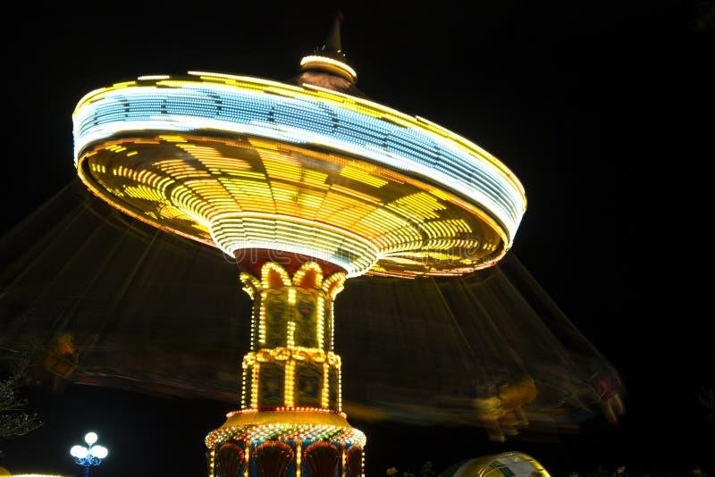 Girando con la catena ad alta velocità dell'attrazione di carnevale con la l luminosa fotografia stock libera da diritti