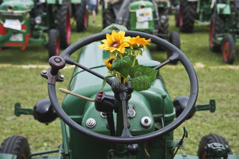 Girasol plástico en el volante de un tractor viejo fotos de archivo
