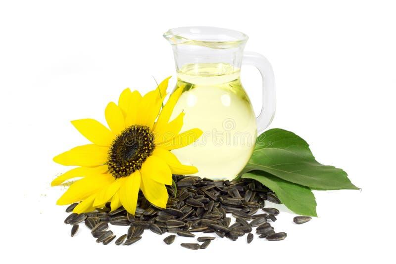 Girasole e semi con le foglie verdi e l'olio di girasole in lanciatore di vetro isolato su bianco immagini stock
