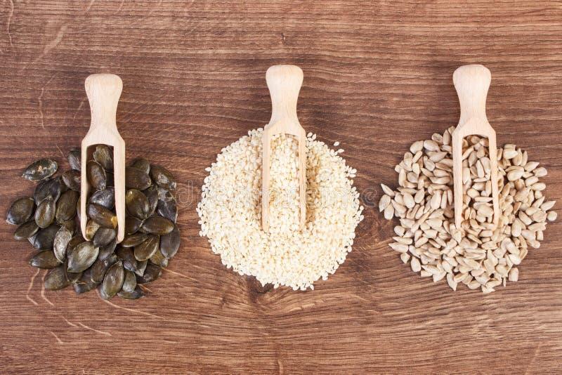 Girasole, zucca e semi di sesamo con il mestolo di legno a bordo, concetto sano di nutrizione fotografie stock
