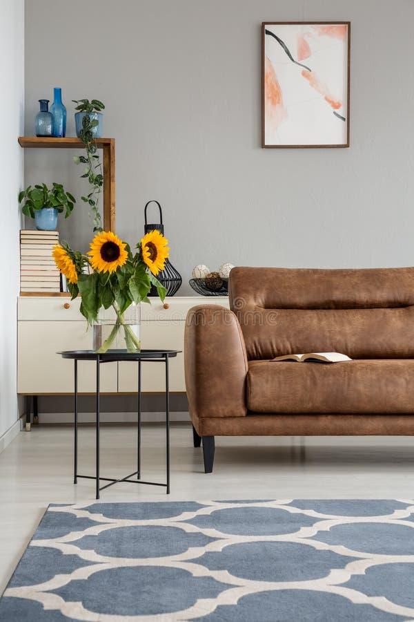 Girasoles en la tabla al lado del canapé de cuero en interior del apartamento con el cartel y la alfombra Foto verdadera fotografía de archivo