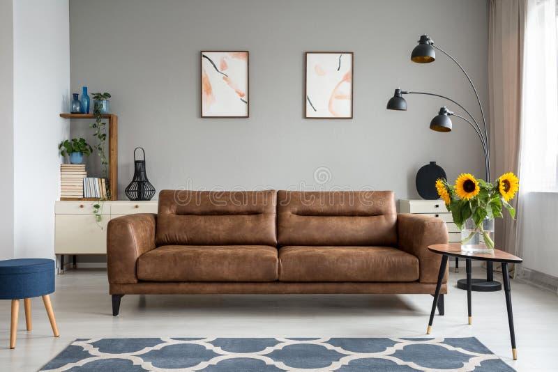 Girasoles en la tabla de madera al lado del sofá de cuero en interior de la sala de estar con los carteles Foto verdadera fotos de archivo
