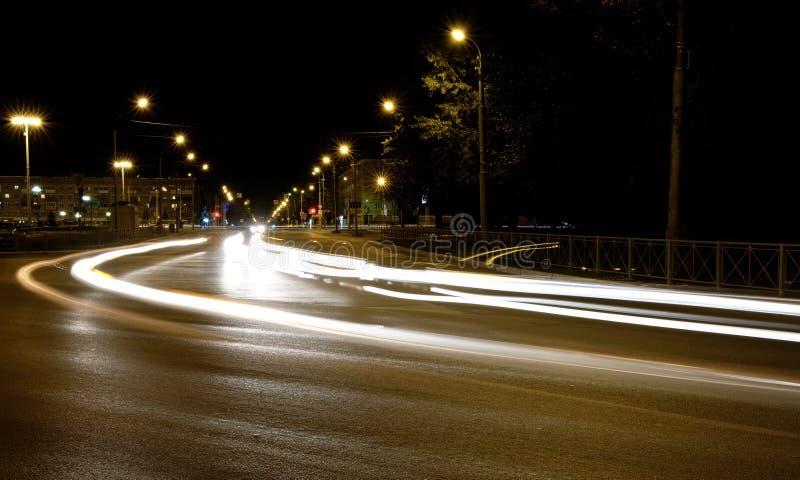 Gire los coches en la noche, los rastros de las linternas como líneas de luz, intersección de la ciudad de la noche foto de archivo