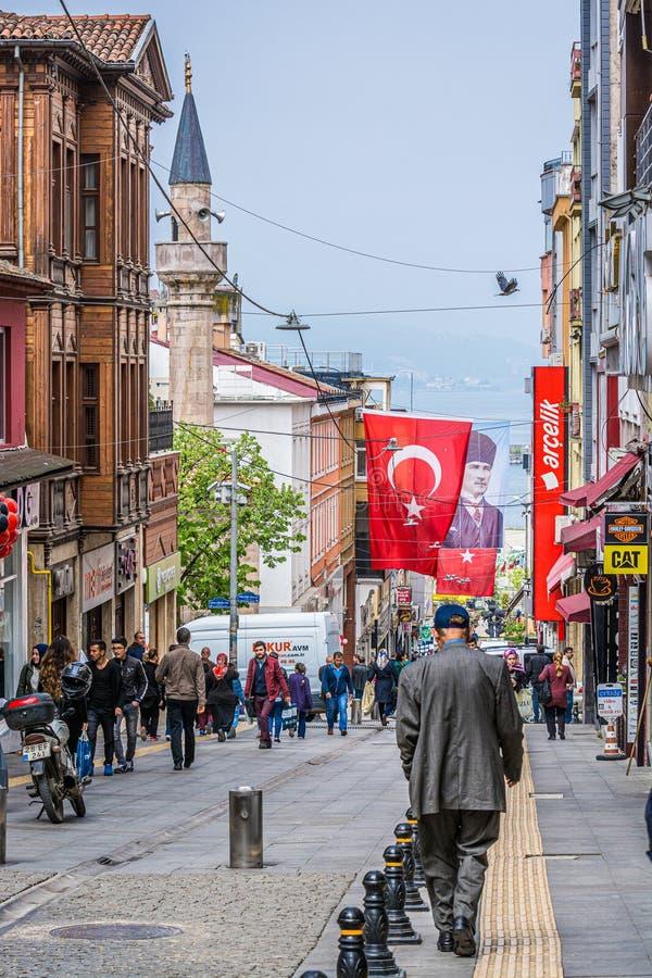 Giresun, Турция - 6-ое мая 2017 Главная улица Crowdy с турецкими флагом и минаретом стоковая фотография