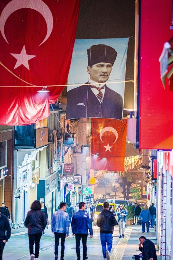 Giresun, Turquia - 5 de maio de 2017 Crowdy Main Street na noite com bandeira e o cartaz turcos da ex-presidente Ataturk fotos de stock royalty free