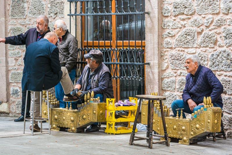 Giresun, Turquia - 6 de maio de 2017 Sapatas da limpeza do homem na rua pela maneira tradicional imagem de stock royalty free