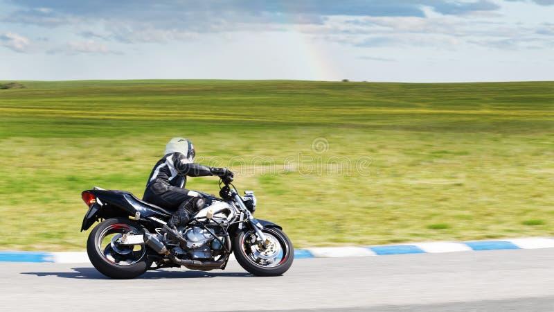 Giri del motociclista su una strada campestre immagini stock libere da diritti