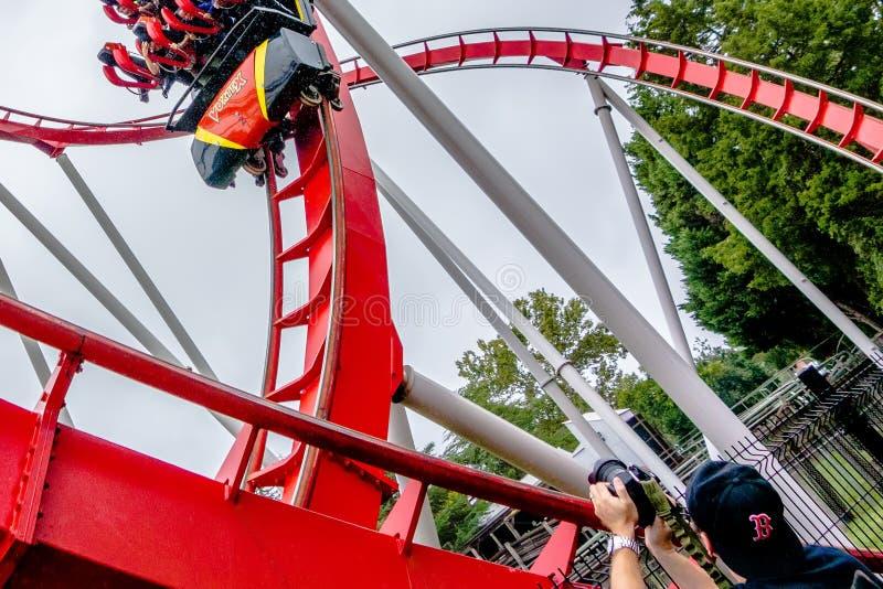 Giri pazzi delle montagne russe al parco di divertimenti fotografia stock libera da diritti
