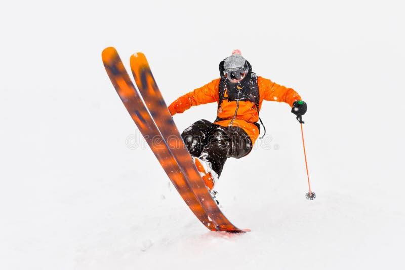 Giri professionali dell'atleta dello sciatore da neve profonda mentre eseguendo un trucco di sci in una bufera di neve La stagion fotografia stock libera da diritti