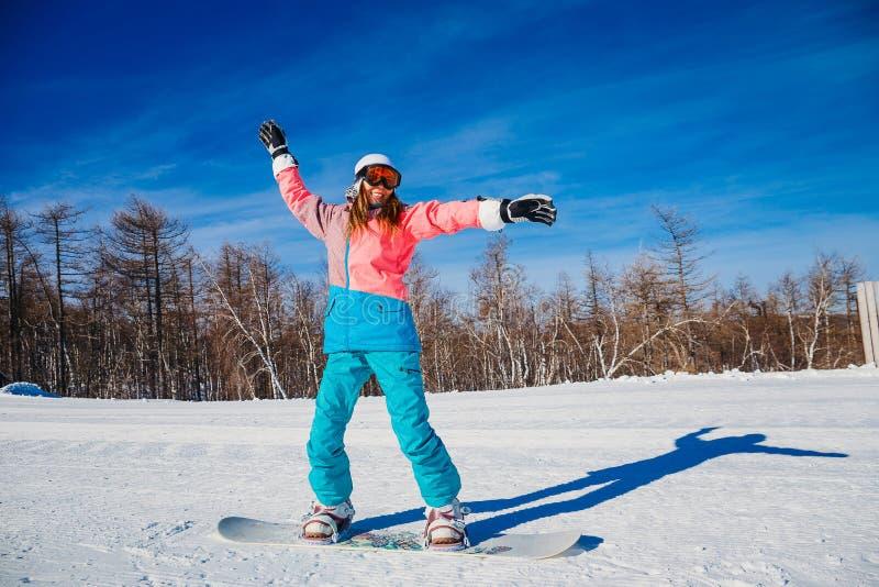 Giri sorridenti giovani di una donna su uno snowboard immagine stock