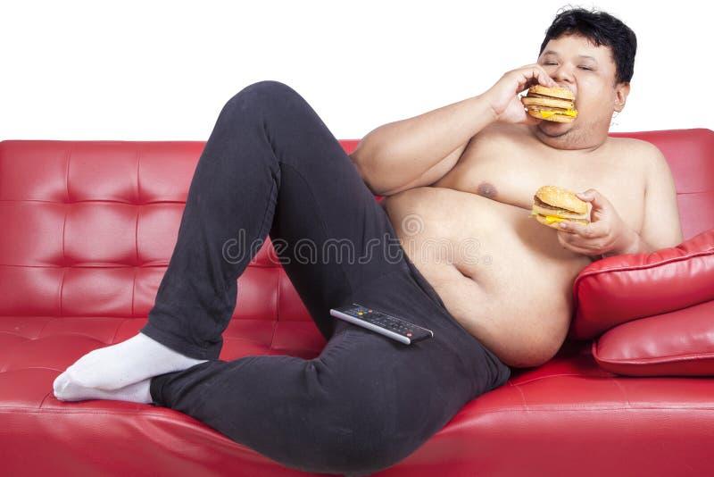 Girig fet man som äter hamburgare 1 arkivfoto