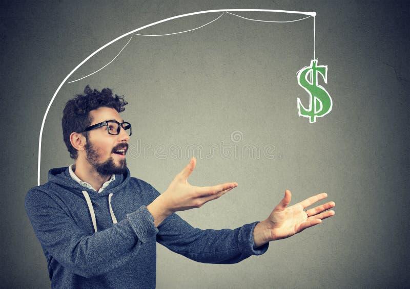 Girig man som jagar dollarräkningen på grå bakgrund arkivbild