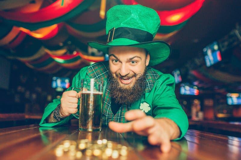 Girig ung man i gröna Sts Patrick dräkt som når guld- mynt Han det på tabellen i bar och hållen rånar av öl royaltyfria bilder