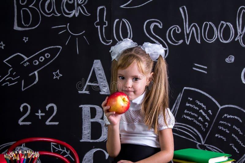 Girigt skolflickasammanträde på skrivbordet med böcker, skolatillförsel som yholding ett rött äpple i assistenten royaltyfri foto