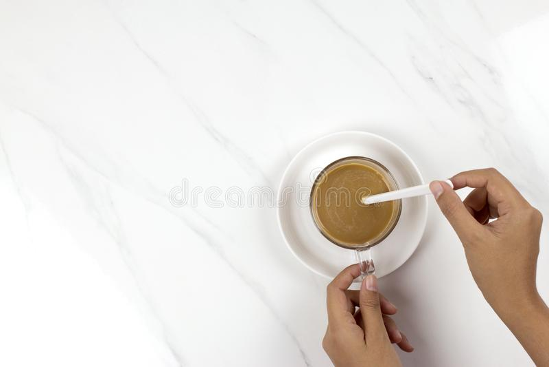 Girl'shand holding en het bewegen koffiekop op marmeren lijst royalty-vrije stock afbeelding