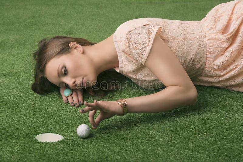 Girlâs se trouvant sur l'herbe avec la bille de golf image stock