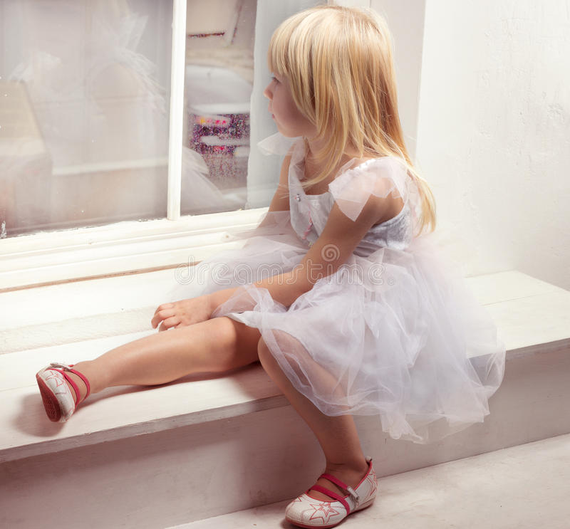 Girl 3 years old in a white dress near window stock photo