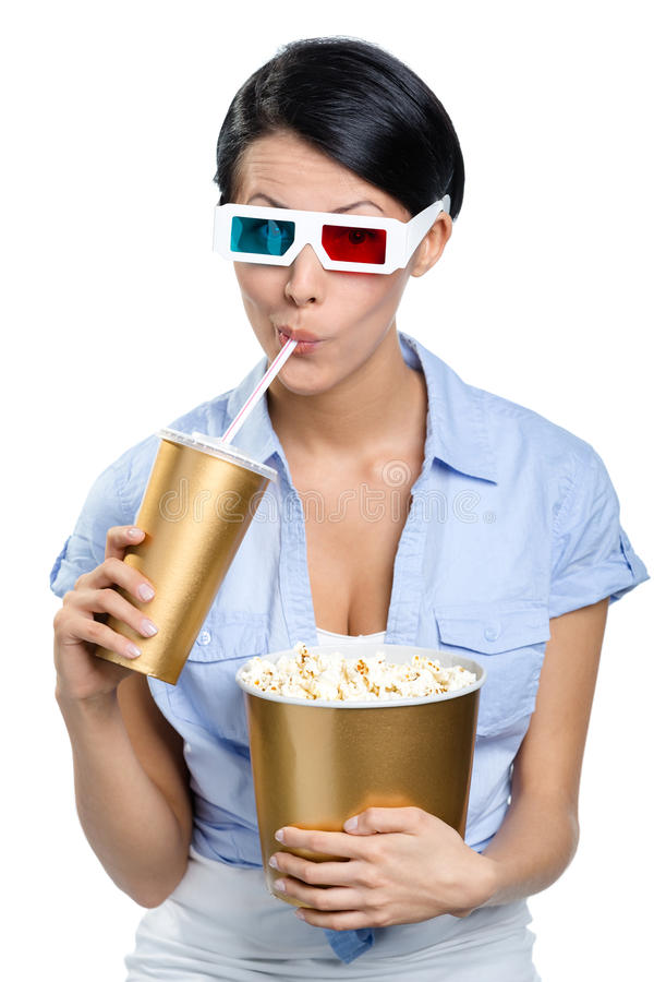 Girl in 3D glasses drinking beverage with popcorn royalty free stock photo
