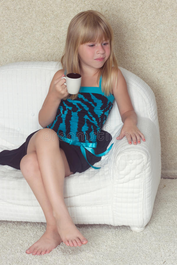 Free Girl 5 Years Old Sitting On A Sofa With Cup Royalty Free Stock Image - 43928406