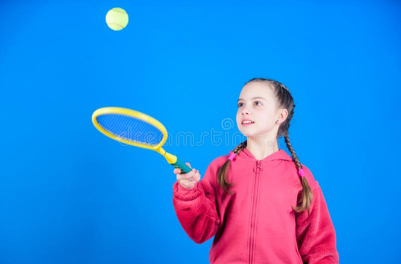 Girl adorable child play tennis. Practicing tennis skills and having fun. Athlete kid tennis racket on blue background. Active leisure and hobby. Tennis sport stock photography